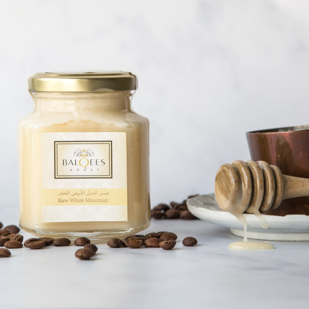 jar of raw white mountain honey with coffee and a honey drizzler
