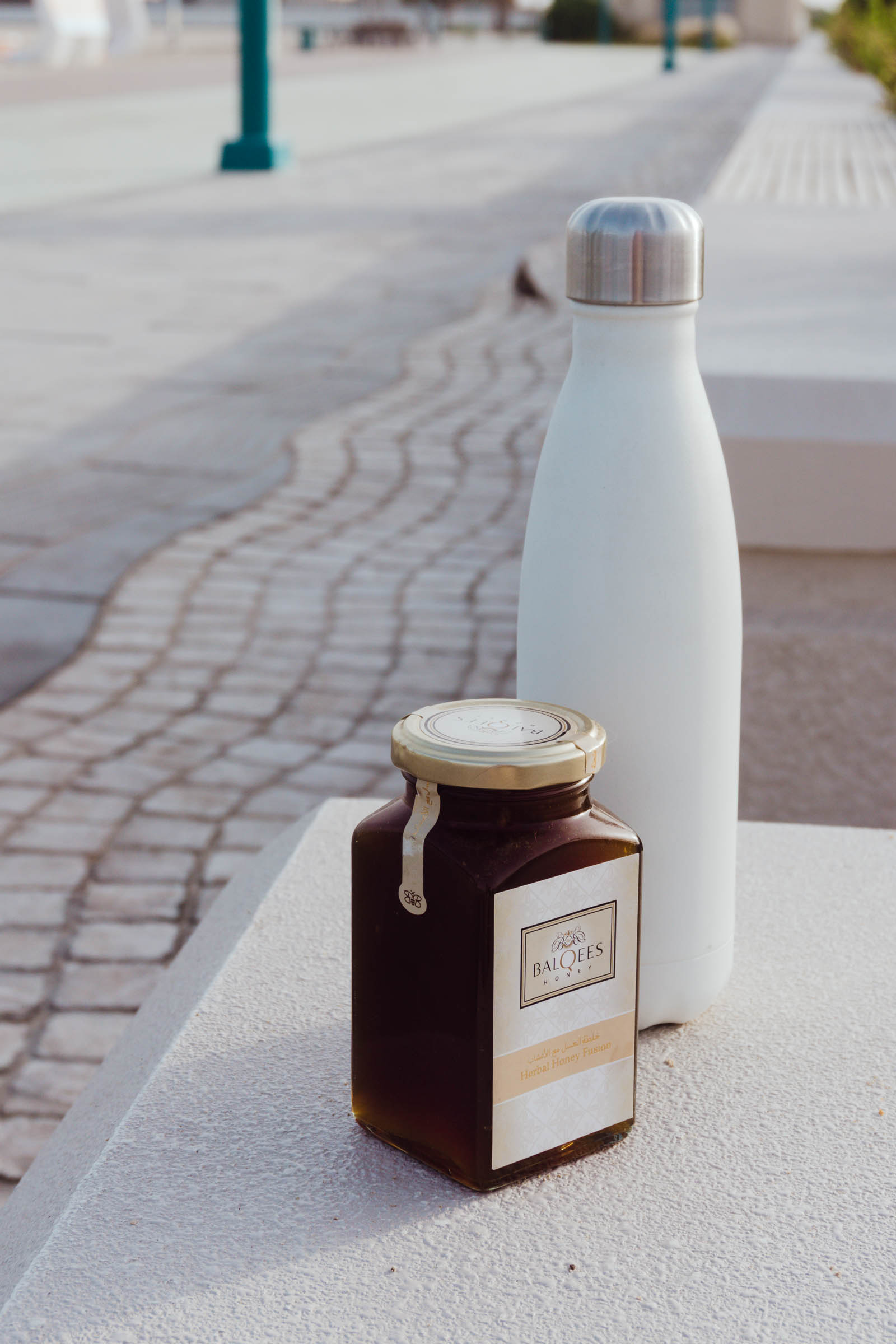 Raw honey with a water bottle by a running track