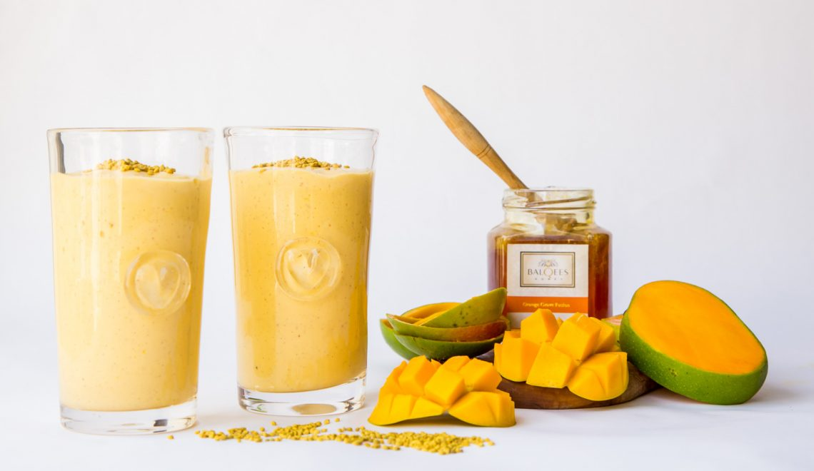 Two glasses of mango smoothie, a jar of honey and some mangoes