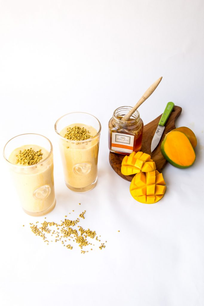 two glasses of mango smoothie and a jar of raw honey