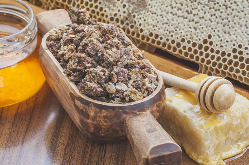 a wooden scoop full of propolis, honeycomb and beeswax