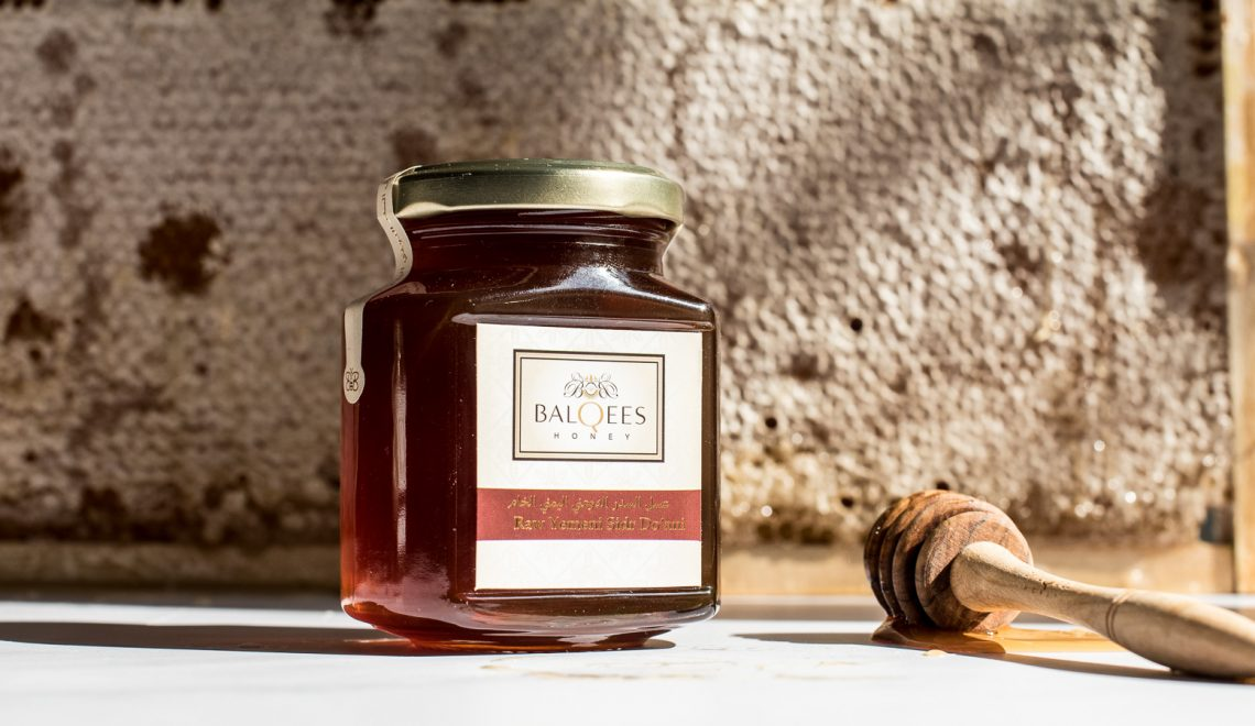 a jar of raw honey, a honey drizzler in front of honeycomb