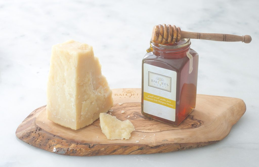 hunk of cheese and a pot of raw honey with a drizzler