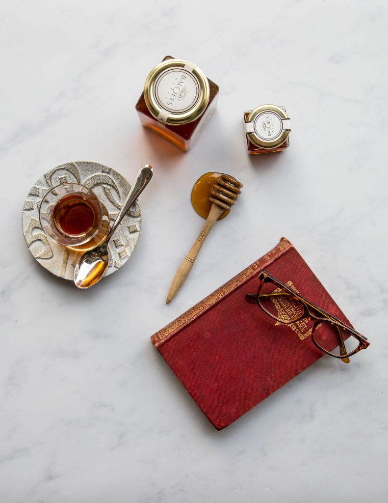 a book, some glasses, tea and raw honey