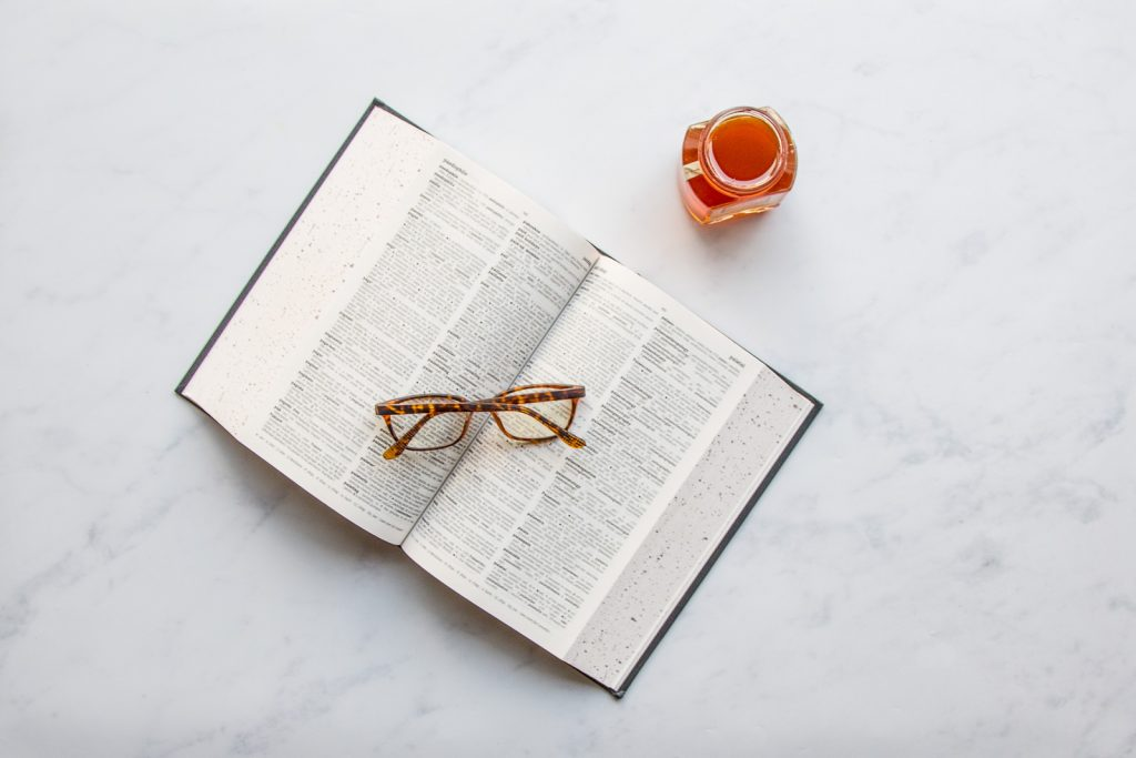 a book, some glasses and raw honey