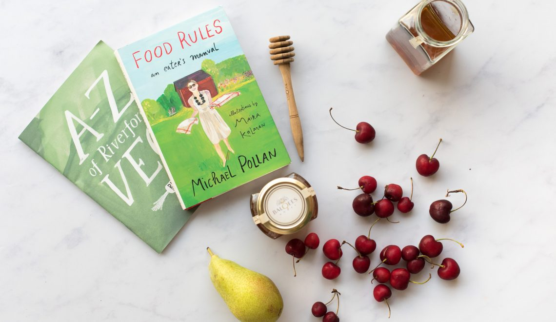 books on health and eating, cherries, a pear and a jar of raw honey