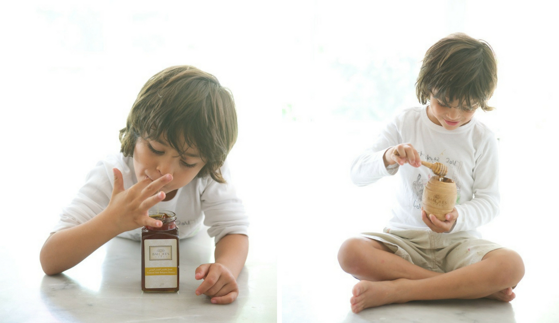young boy eating raw honey from a jar